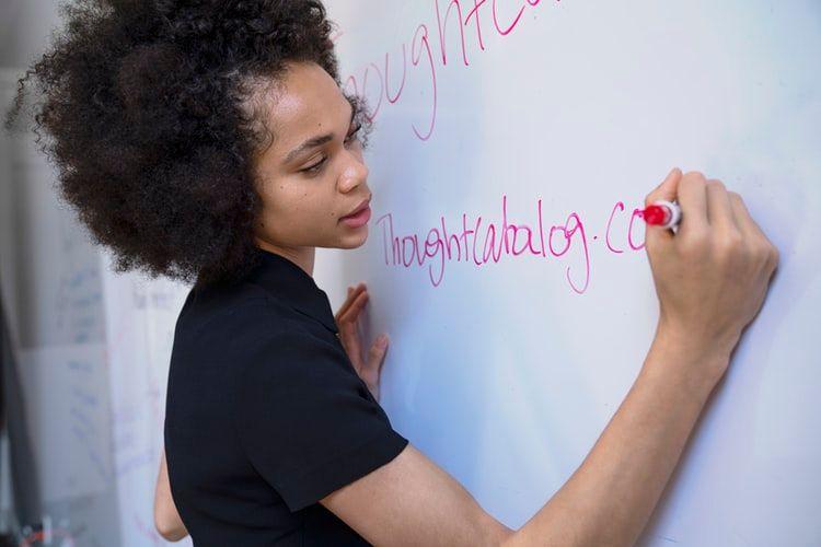 mulher escrevendo em um quadro branco